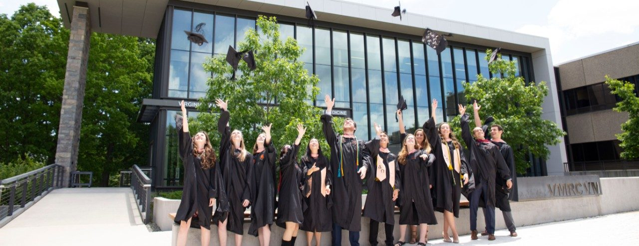 Students outside in graduation robes tossing caps into the air
